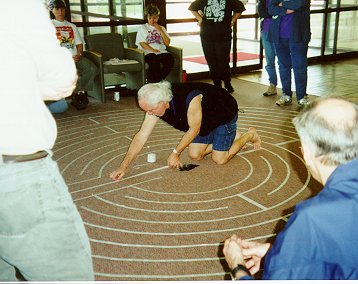 Photo of Robert Ferre demonstrating how to make a Chartres labyrinth.