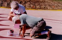Photo of Robert and a volunteer painting the labyrinth.