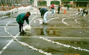 Photo of making a labyrinth on a parking lot out of stones.